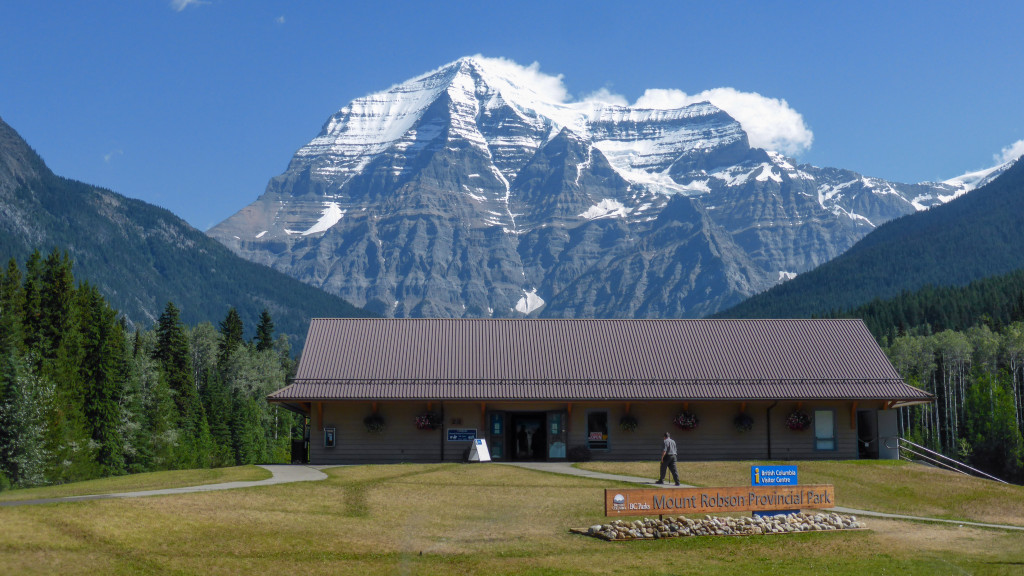 The exterior of the Mount Robson Visitor Centre with large, snow-capped mountains in the background.