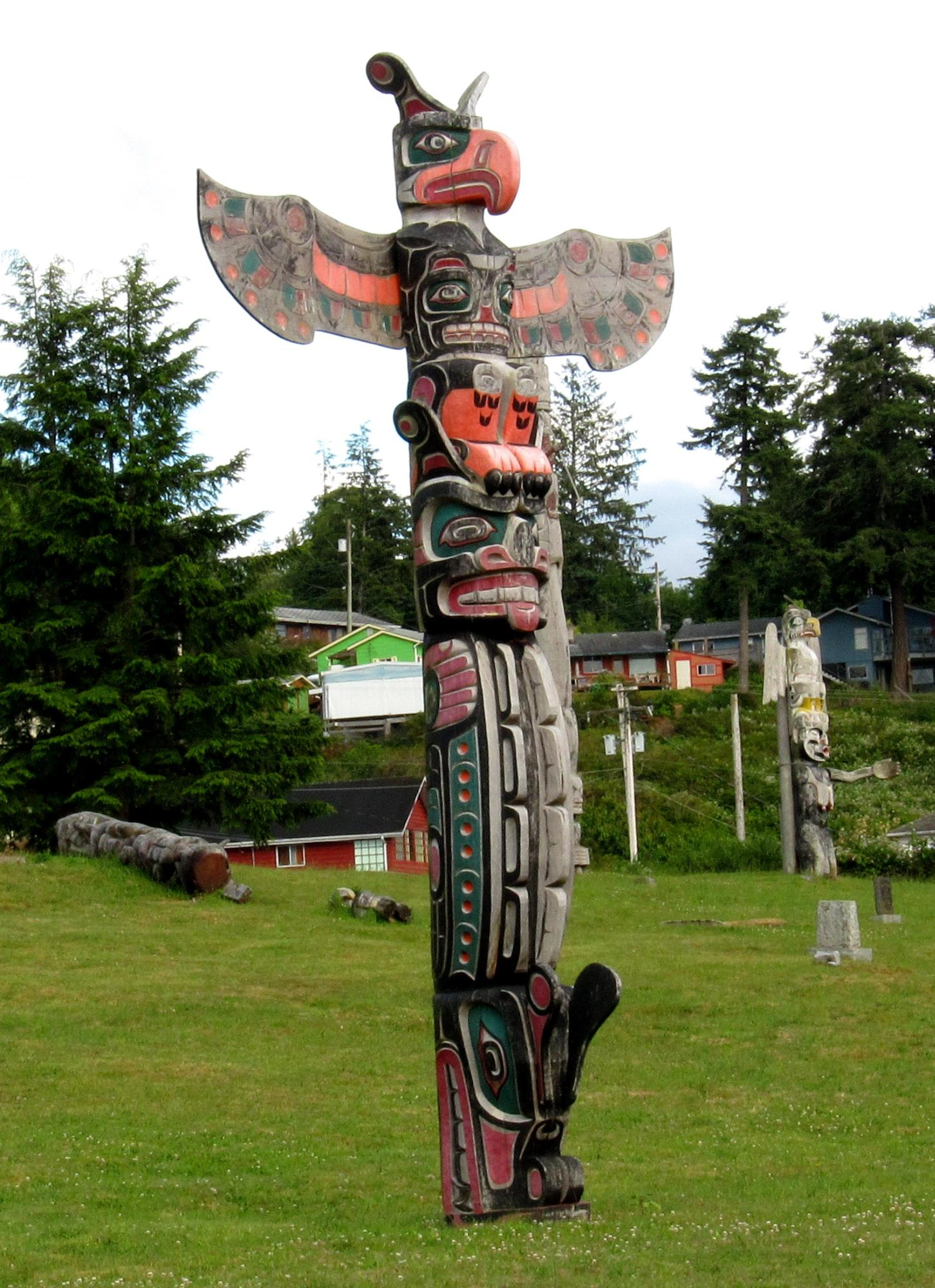 A colourful totem pole erected on a lush green lawn.