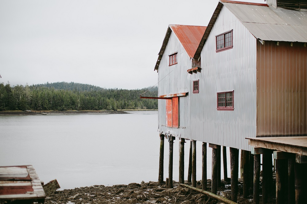 Two older buildings sit on stilts on a rocky shore.