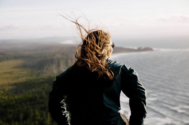 A windswept woman takes in coastal views.