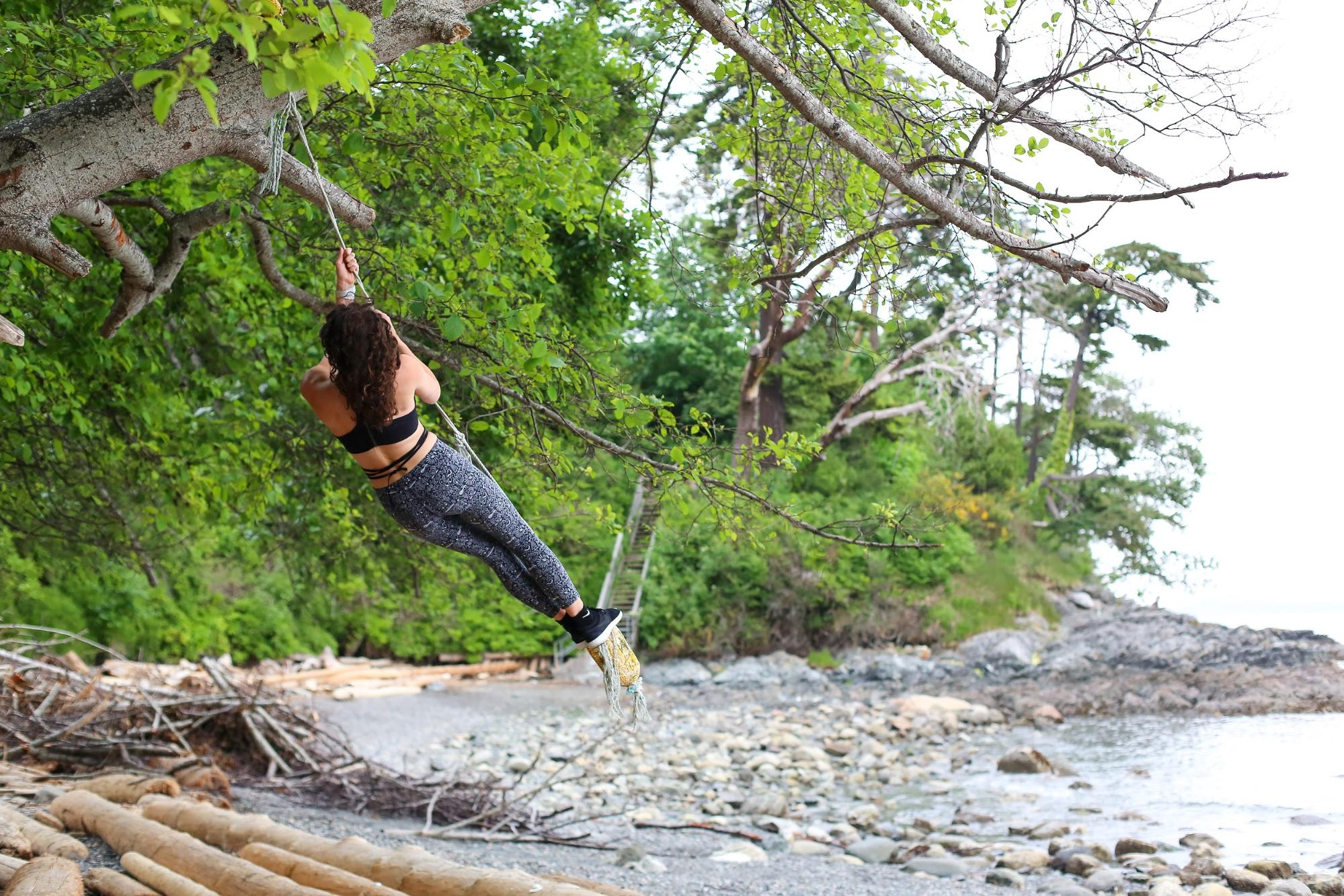 A woman swings from a rope tied to a tree over a rocky riverbank.