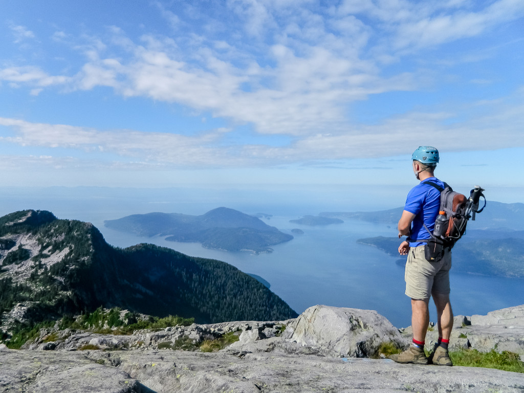 A hiker pauses to take in the view of the Howe Sound under a blue sky.