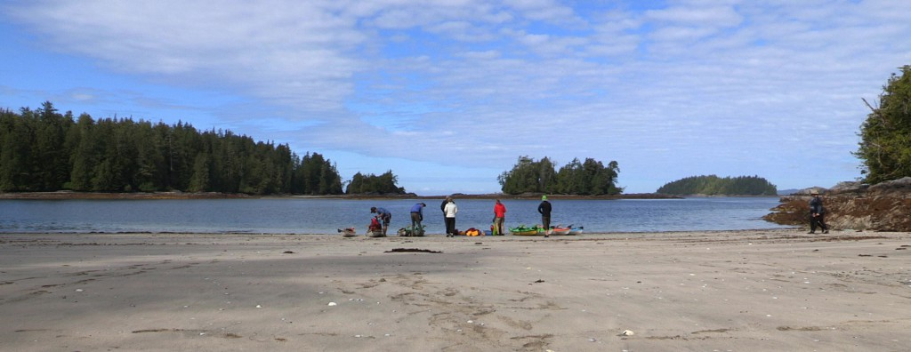 A group of kayakers stand on a beach at the water's edge.
