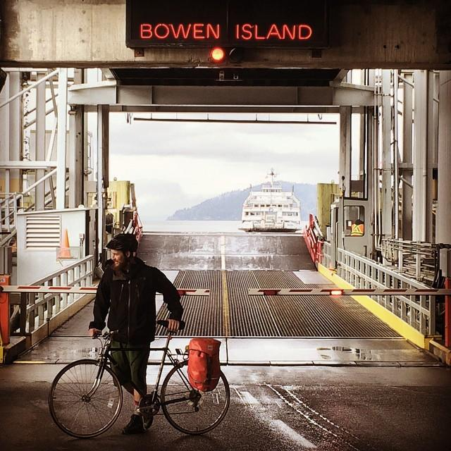 "A man takes his bike across a ferry terminal with a sign in red that reads ""Bowen Island""."