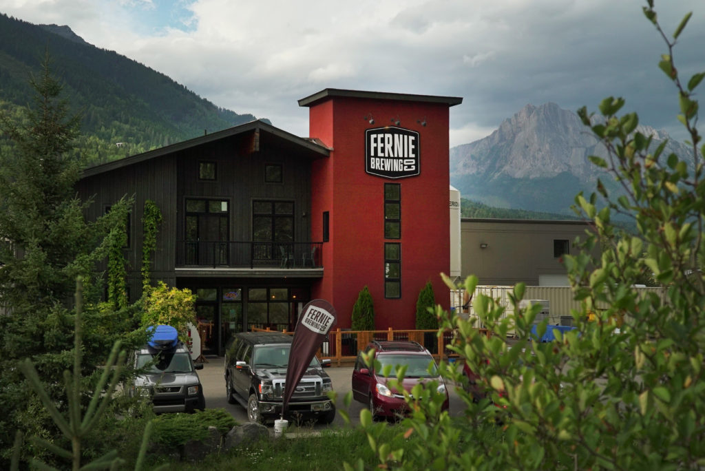 The exterior of the FE]ernie Brewing Co. building, with mountains in the background.