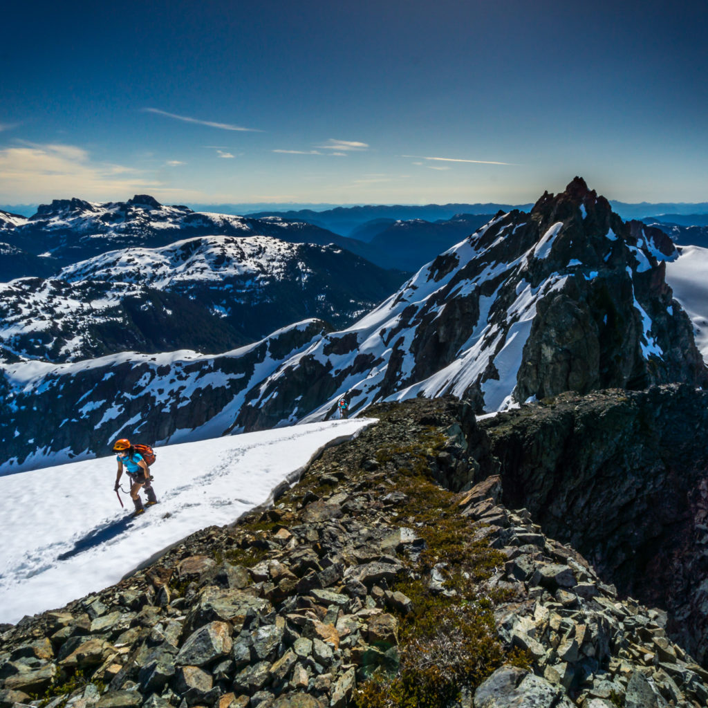 A hiker traverses a snow-covered rocky landscape with snow-capped mountains in the background.