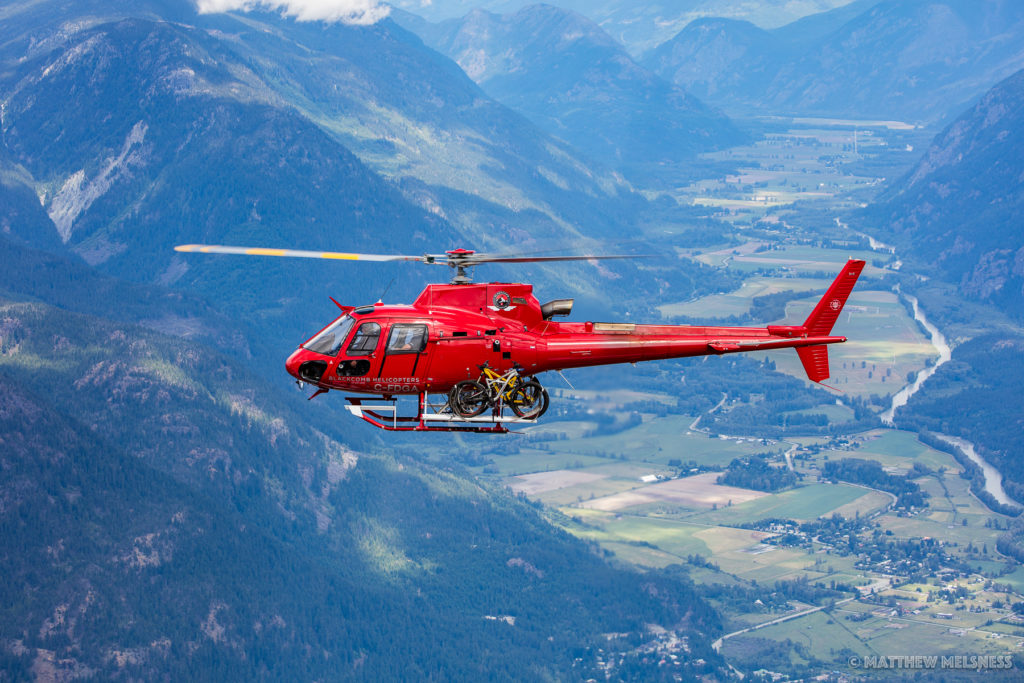 A red helicopter with mountain bikes strapped to the exterior flies over a mountain landscape.