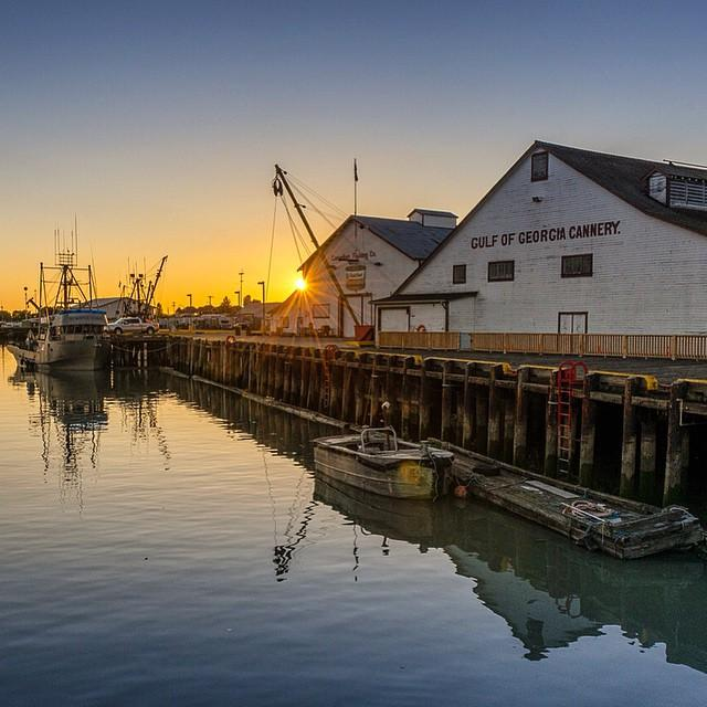 The Gulf of Georgia Cannery overlooks a quiet harbour at sunset.