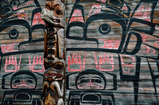 An intricately carved totem pole stands in front of a colourfully painted wooden wall.