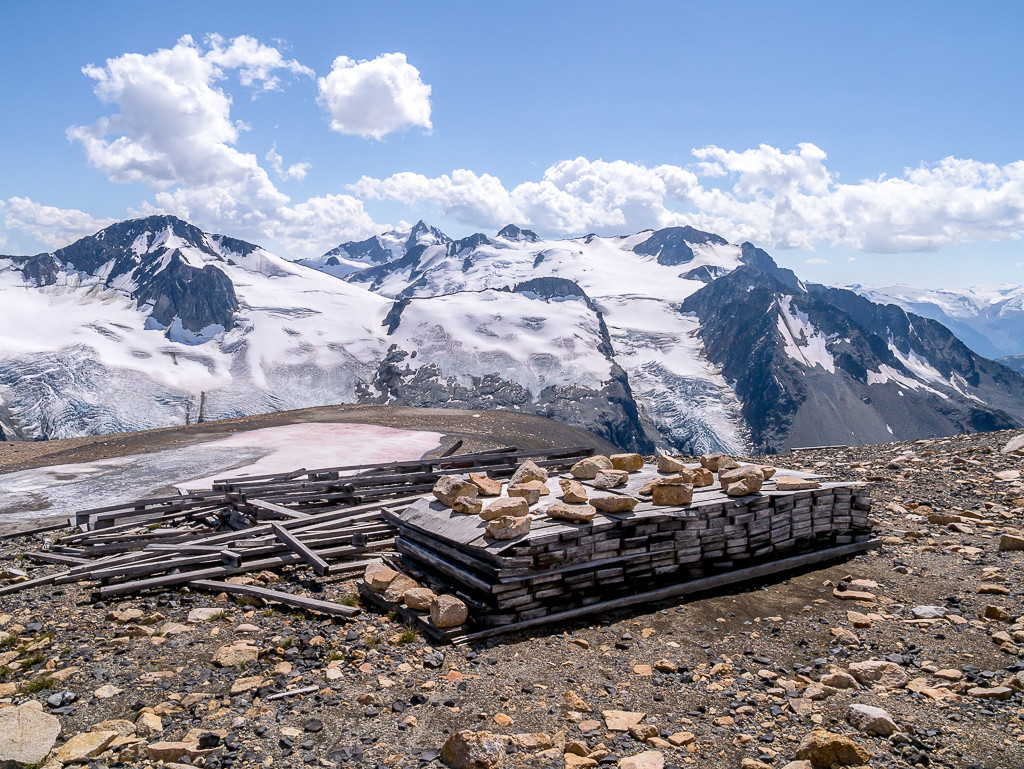 Abandoned mining equipment with snow-capped mountains as the backdrop.