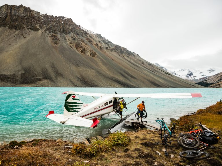 Mountain bikes are offloaded from a sea plane that has landed in turquoise waters.