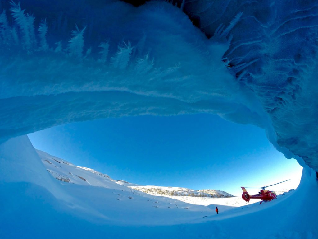 A red helicopter touches down in a snowy landscape, in front of an ice cave.