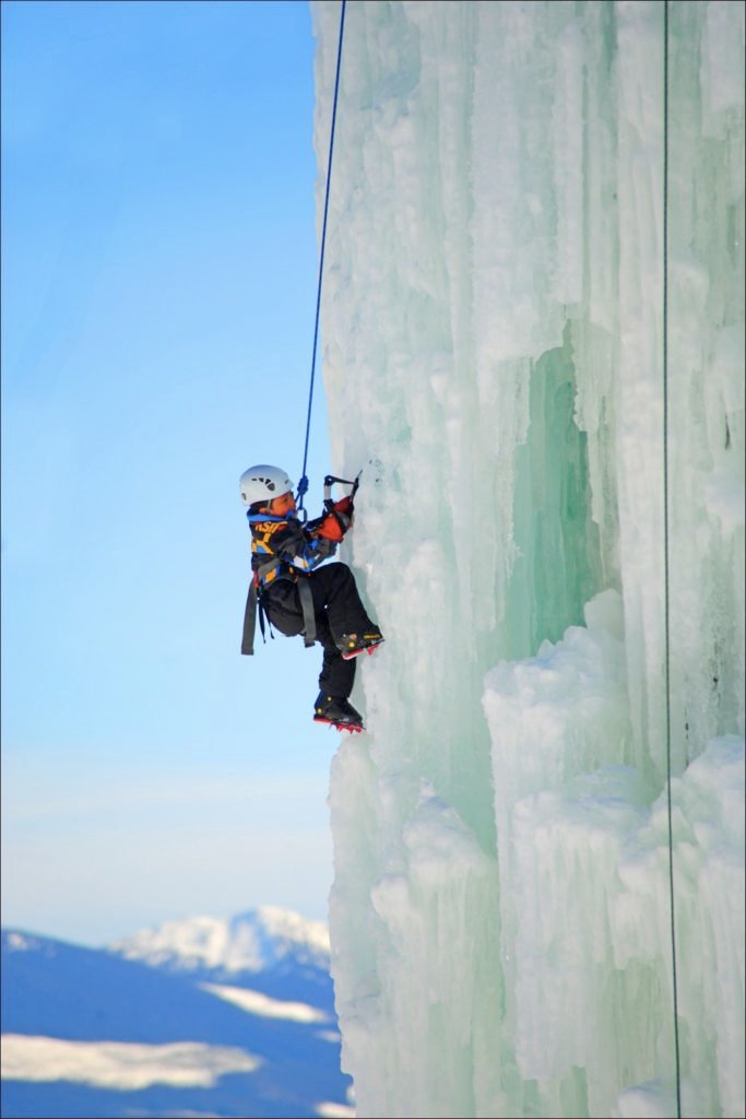 A young boy scales a thick wall of white ice.