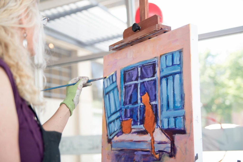 An artist at her easel, painting an orange cat looking out the window.