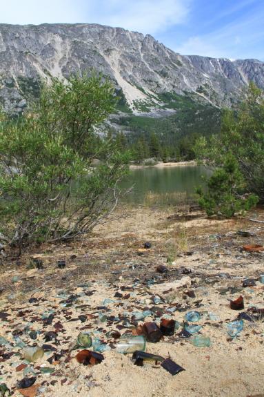 Piles of broken glass dot a sandy shore