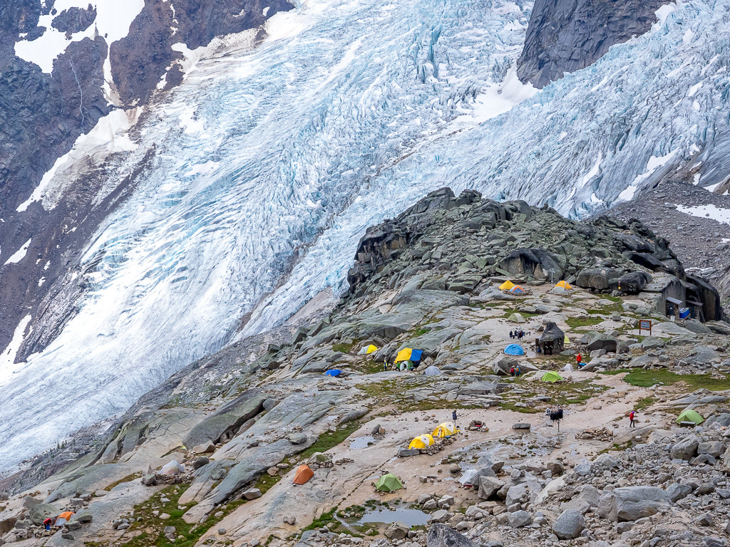 A campground perched on a rocky landscape overlooks a massive glacier.