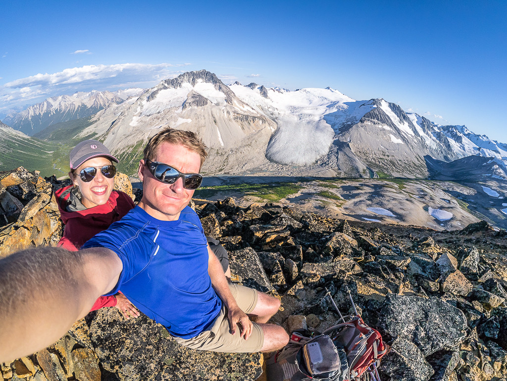 A couple take a selfie in front of a sweeping mountain range.