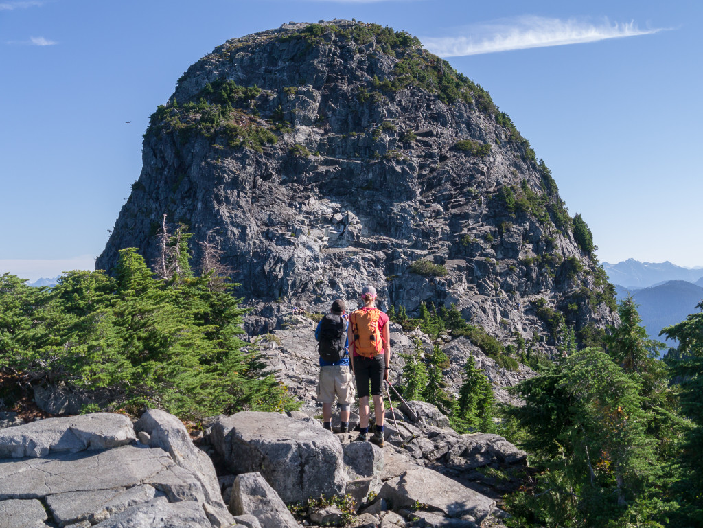 Two hikers pause to take in a large rock formation.