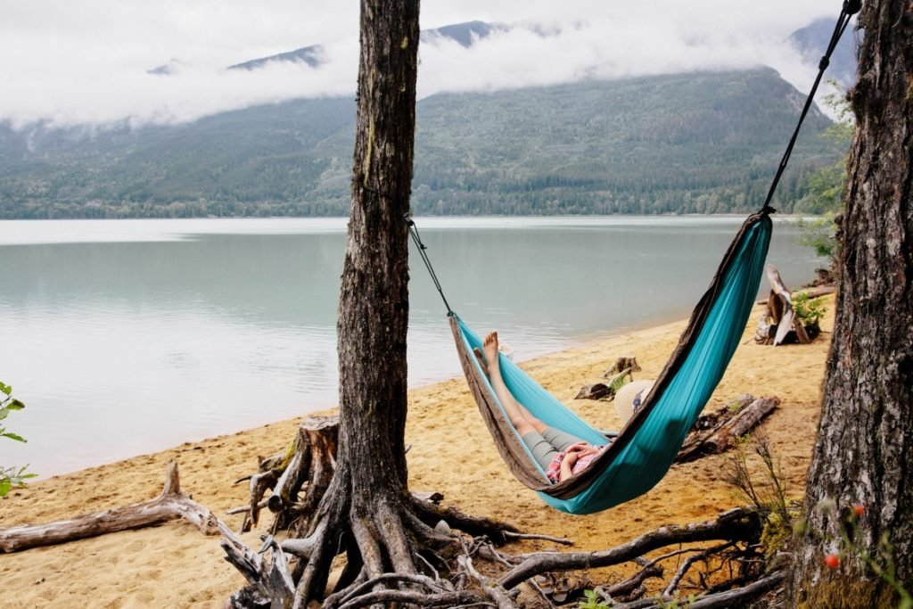 A woman relaxed in a hammock on a beach surrounded by mountains.