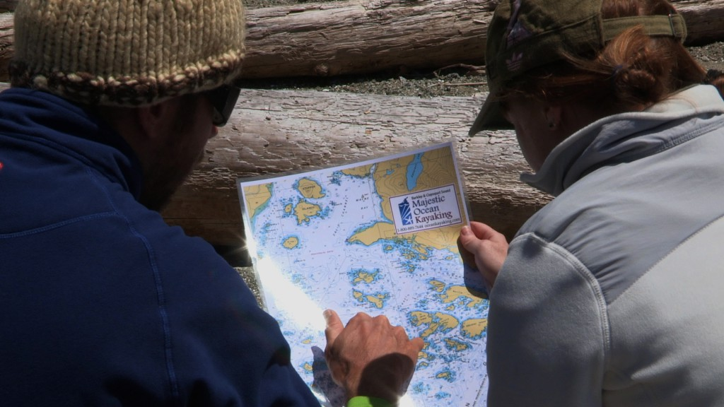 Two men study a Majestic Ocean Kayaking map.