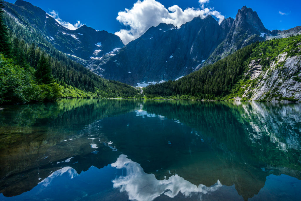 A sprawling mountain range and blue sky are reflected in still waters nestled in a lush valley.