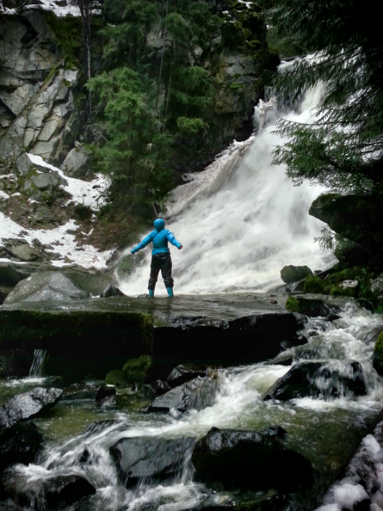 A hiker stands, arms outstretched, in front of a waterfall in a rocky landscape.