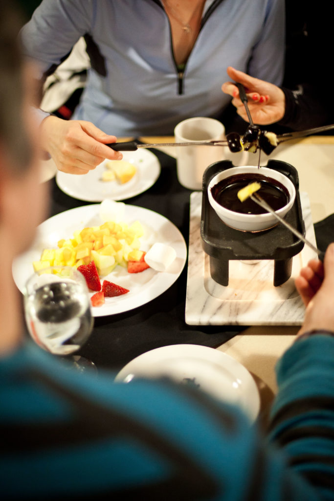 A group of friends enjoy a pot of chocolate fondue.