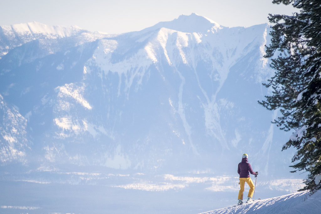 A woman skier stops to take in the snow capped peaks surrounding Kimberley Alpine Resort.