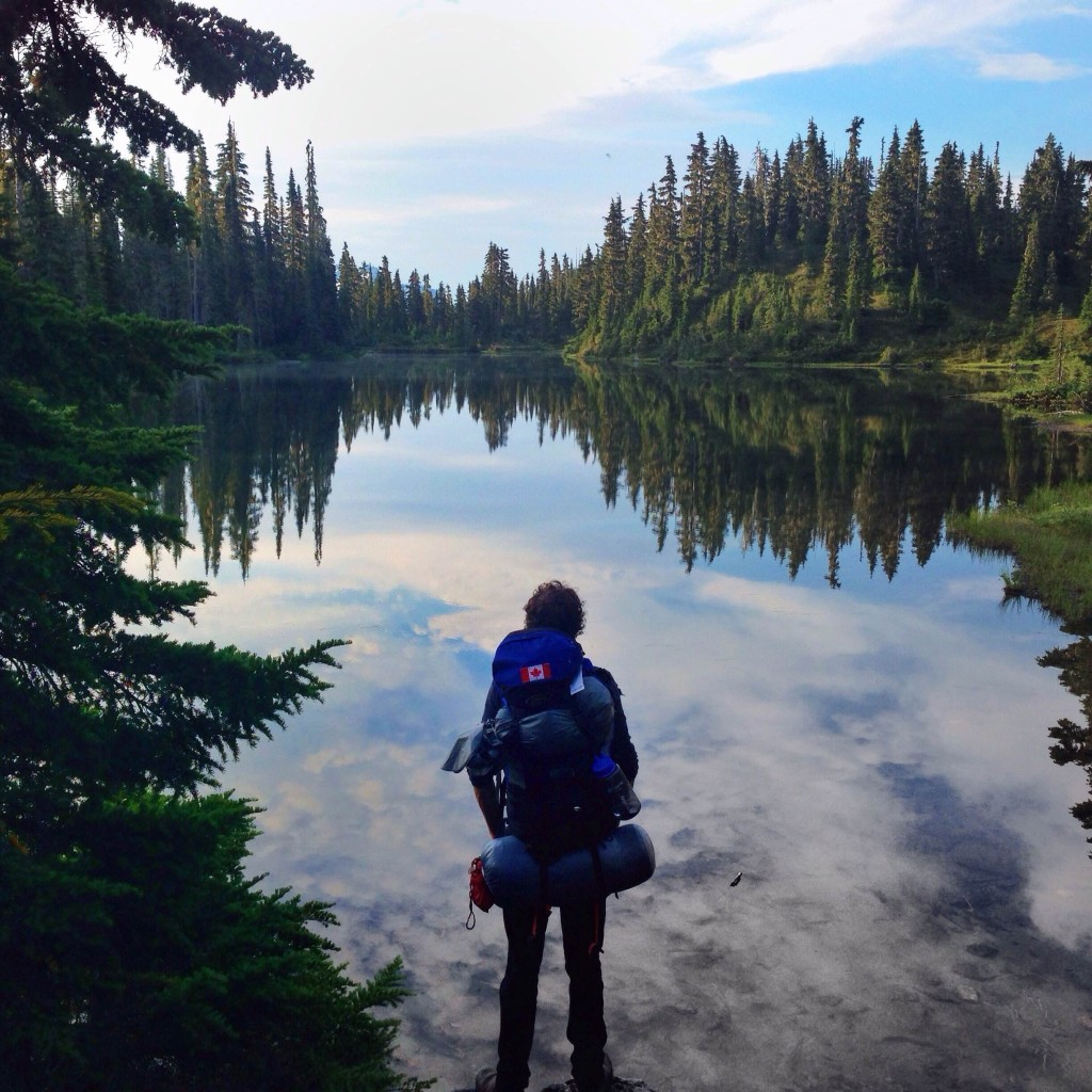 A hiker pauses to take in the glassy waters of Arnica Lake.