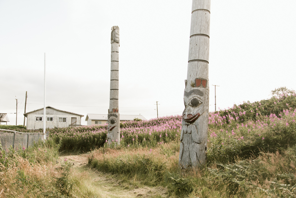 Tall poles carved from red cedar sit in a field of blooming flowers.