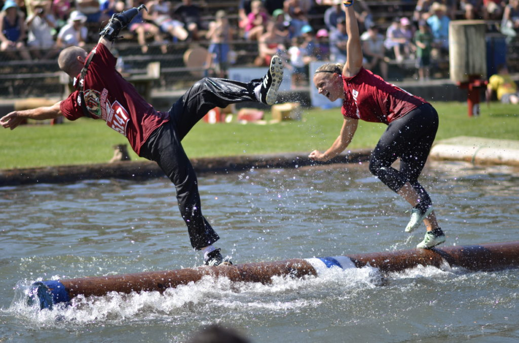 A man and woman try to keep their balance while running on a log in a pool of water.