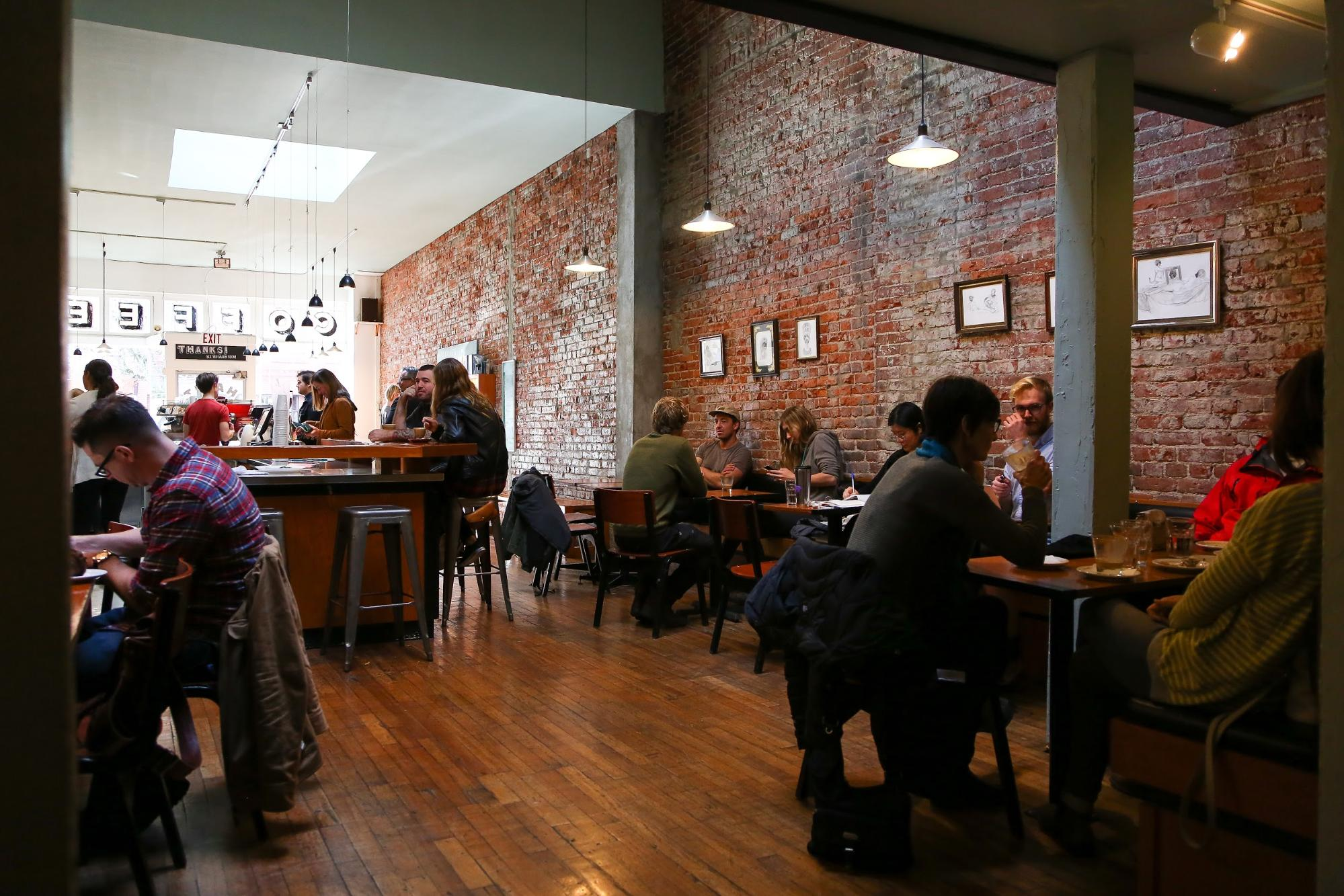 Diners sit in a modern coffee shop with brick walls.