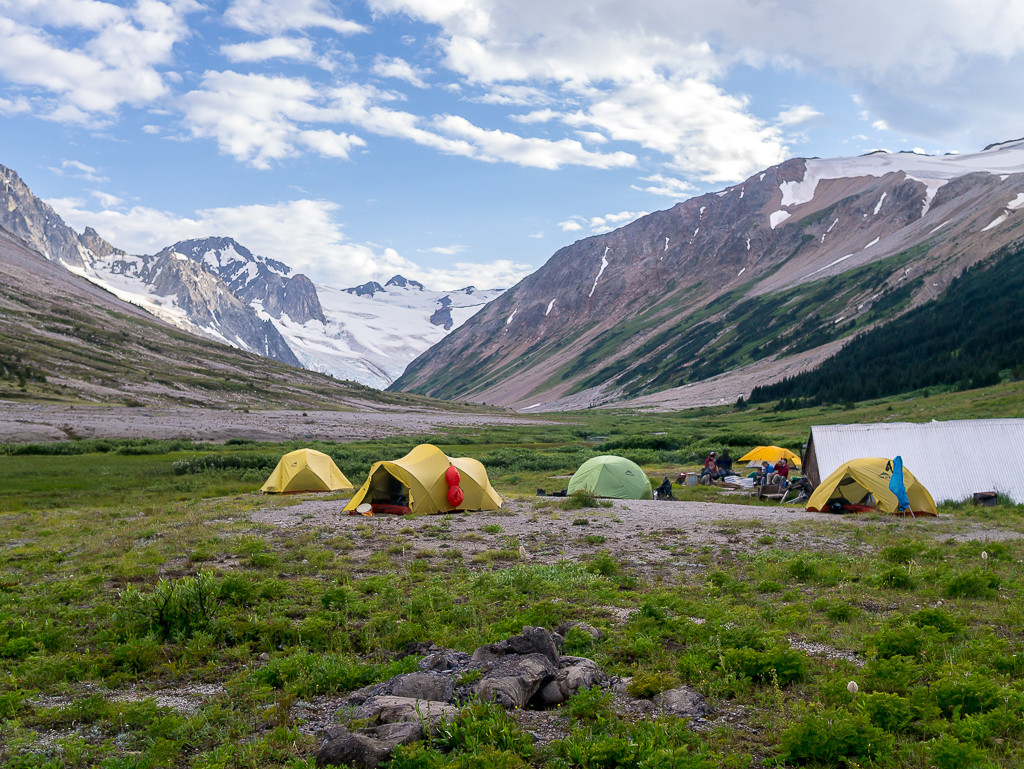 A campsite is nestled in a valley, between sweeping mountain ranges.