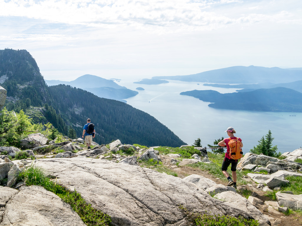 Two hikers traverse a rocky coastal path.