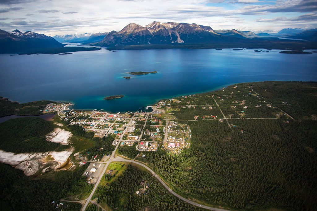 Aerial view of Atlin, the ocean, and a stunning mountain range.