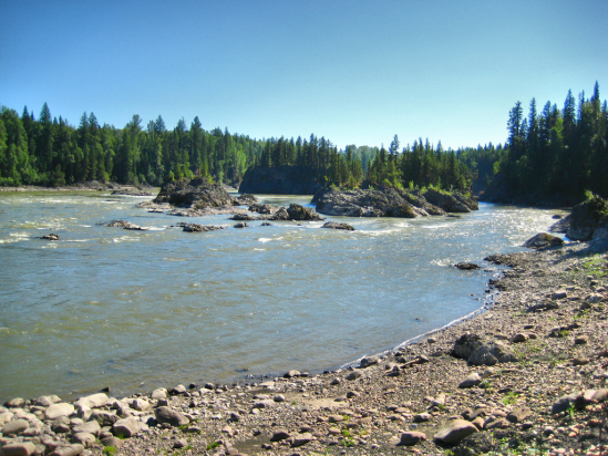 A rocky shore surrounds shallow rapids under a clear sky.