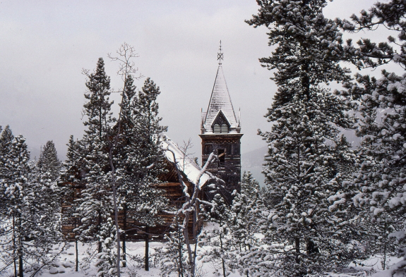 A snow-covered church is nestled amongst white-dusted trees.