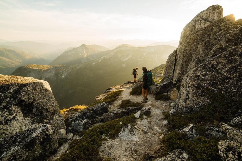 Two women hike along rocky mountain peaks.