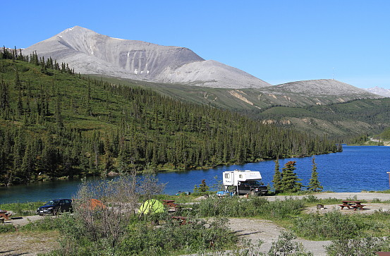 Campers and tents are set up at the edge of the water, overlooking a dense forest and a rocky mountain.