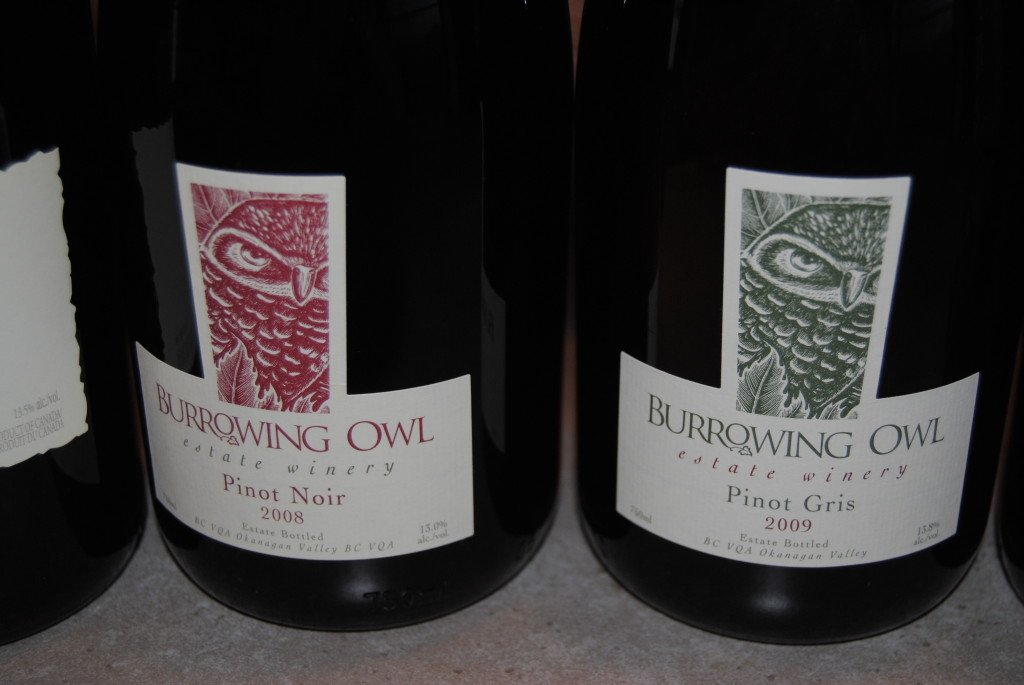 A close up view of three wine bottles with Burrowing Owl Estate Winery labels on them.