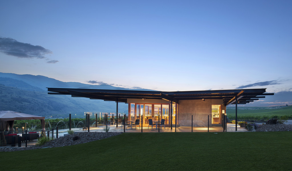 Black Hills Estate Winery lit up at dusk, with a flat modern roof, chairs outside on a patio, the Okanagan hills in the background and a lush green lawn in the foreground.