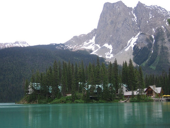 Turqouise Emerald Lake with Emerald Lake Lodge across the water and the tall mountain peaks of Yoho National Park in the background.