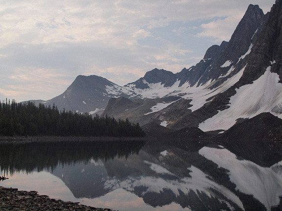 A still Floe Lake reflecting the towering snow-capped peaks of Kootenay National Park.