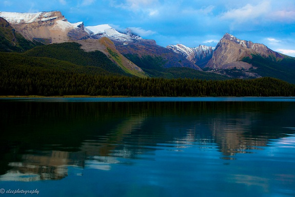 Jasper National Park's mountain peaks reflecting in a still lake with blue skies above.