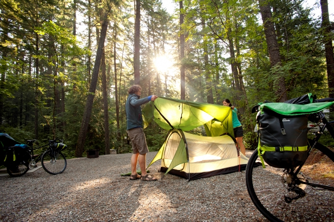 A couple pitches a tent in a small clearing in the forest.