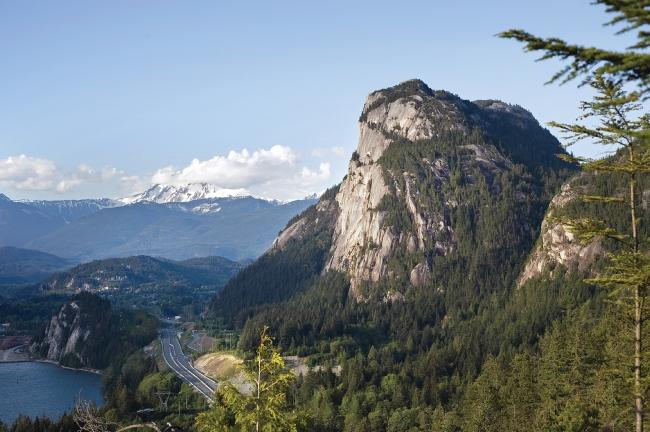 A rocky mountain overlooks a coastal highway.