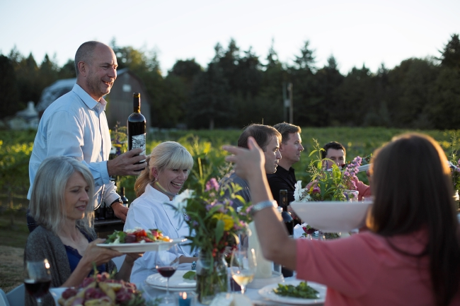 A group of people sit at a dinner table outdoors enjoying food and wine.