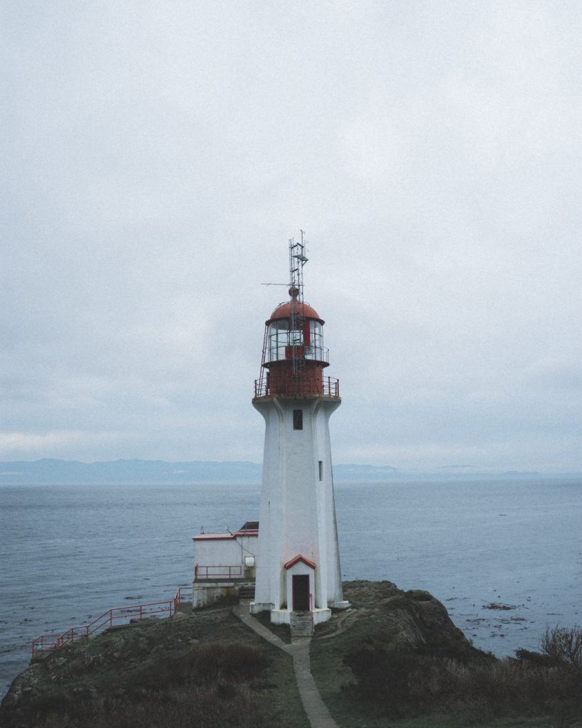 A lighthouse sits at the edge of the ocean under an overcast sky.