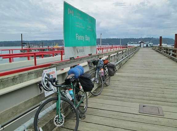 Two bikes leaning against a red railing on the Fanny Bay's wooden dock, with a big green sign for Fanny Bay on the left hand side of the dock.