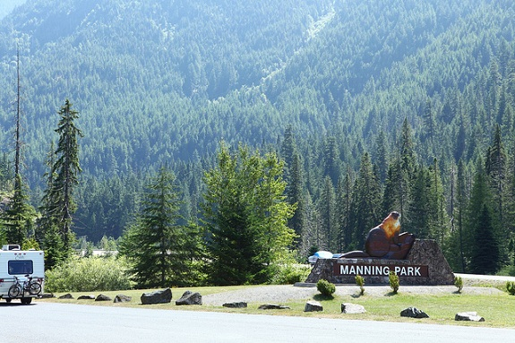 The entrance to Manning Provincial Park, with a wooden sign, an RV driving down the road and thick forested hills in the background.